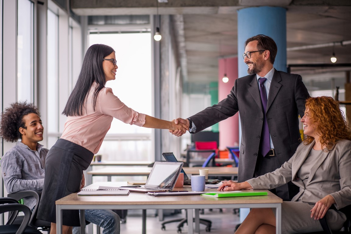 Two business teams successfully negotiating, shaking hands. At meeting table business groups shaking hands on completed deal. Man and woman handshake.