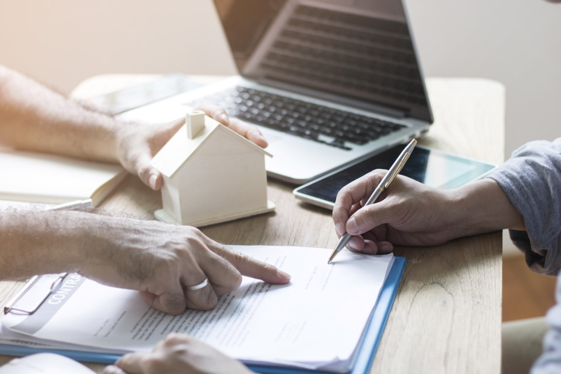 Home buyer are sign contract on sheet  with agent or broker in office, concept as agreement of insurance or house commercial